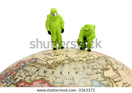 HAZMAT in protective gear on globe. Can represent global warming, chemical warfare, or pollution. - stock photo