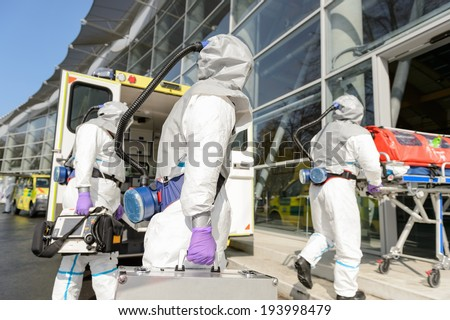 HAZMAT team with stretcher and rescue equipment entering contaminated building - stock photo