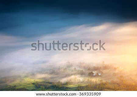 Hazy Azure. Beautiful sunrise view from the top. Green misty meadow covered with morning fog and clouds. - stock photo