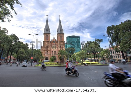 HCMC, VIETNAM-JAN. 9 2014: Motorbike passing the Notre Dame cathedral in Ho Chi Minh City during rush hour - stock photo