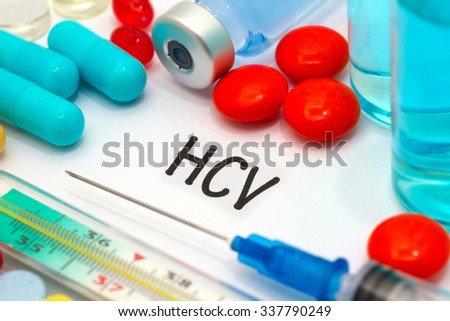 HCV - diagnosis written on a white piece of paper. Syringe and vaccine with drugs. - stock photo
