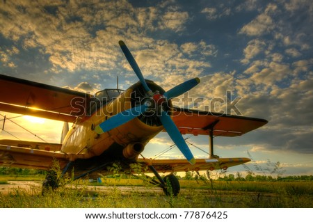 HDR foto of an old airplane on green grass and sunset background - stock photo