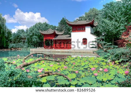 HDR image of a Chinese temple in a garden behind a pool of water - stock photo