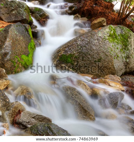 HDR image of a frothy mountain stream through boulders capture with a long exposure - stock photo