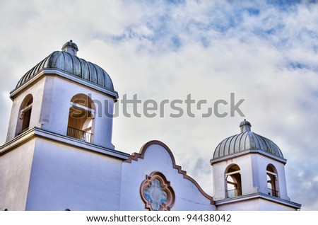 HDR image of a Spanish mission style stucco church with partly cloudy sky - stock photo
