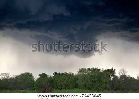 HDR image of a wall cloud,  ready to drop a tornado. - stock photo