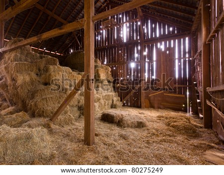 HDR image of an old Barn with the sun streaming from outside and straw and hay on the floor of the hayloft - stock photo
