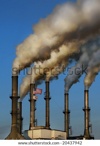 HDR image of working factory smokestacks in late afternoon sun - stock photo