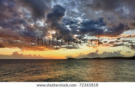 HDR impression of a sunset over the ocean with a distant island on the horizon - stock photo