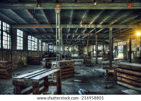 HDR - old abandoned factory interior with wooden tables and boxes - stock photo