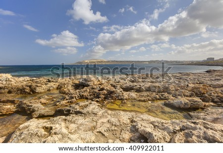 HDR photo of a sunny day at the sea coast with deep blue clean water and a nice stone beach and vegetation growing there