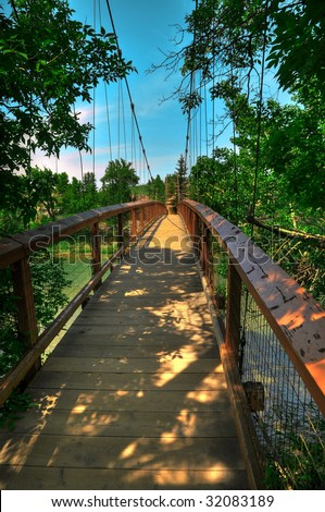 HDR Photo of a Suspension Bridge Over a River - stock photo