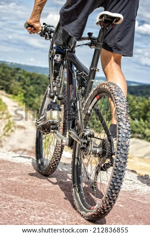 HDR photo of young male mountain bike rider with leg prosthesis preparing for a downhill ride.   - stock photo