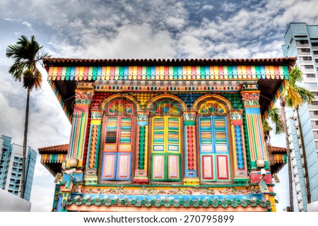 HDR rendering of a colorful building facade in Little India, Singapore, with tall high-rise apartments in the background. A stark contrast of the old neighborhood and modernization in Singapore. - stock photo