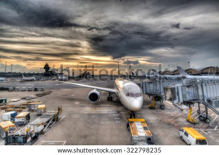 HDR rendering of a golden sunset over Hong Kong International Airport while a plane awaits refueling and servicing before resuming its flight.   - stock photo