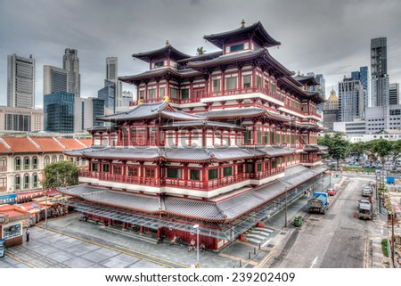 HDR rendering of the Buddha Tooth Relic Temple in Singapore's Chinatown and the city's skyscraper business district in the background. - stock photo