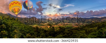 HDR shot of hot air balloon in panoramic view of sunset in the valley of mountain in North of Thailand(with selective focus) - stock photo