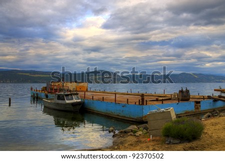 HDR Small Fishing Boat docked in a harbour with Cloudy sky in the background - stock photo
