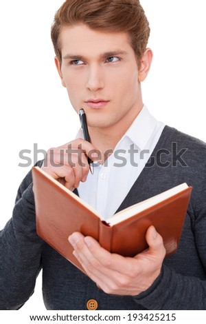 He got creative mind. Thoughtful young man holding note pad and touching chin with pen while standing isolated on white - stock photo