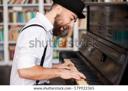 He got creative soul. Handsome young bearded men playing piano and singing - stock photo