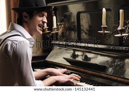 He�¯�¿�½ got creative soul. Handsome young men playing piano and singing - stock photo