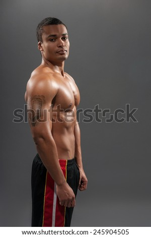 He got perfect body. Side view portrait of young shirtless African man looking away wearing basketball shorts while standing against grey background  - stock photo