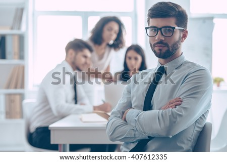 He is a part of great team. Handsome young man in glasses keeping arms crossed and looking at camera while sitting at the office table with his coworkers - stock photo