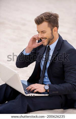 He is always in touch. Cheerful young businessman working on laptop and talking on the mobile phone while sitting on sand - stock photo