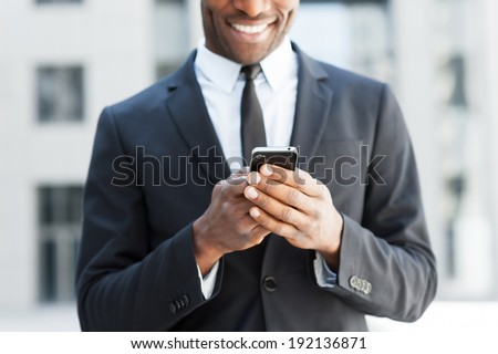 He is always in touch. Cropped image of cheerful young African man in formal wear holding mobile phone and smiling while standing outdoors - stock photo