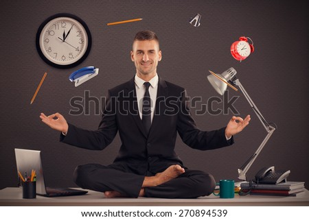He is businessman that can relax in office, while his work is doing. Handsome businessman sit on table in office in lotus position and try to relax. - stock photo