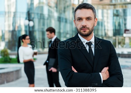 He is great team leader. Confident young businessman keeping arms crossed and looking at camera while two his colleagues talking to each other in the background - stock photo