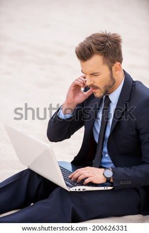 He is in touch anywhere and anytime. Confident young man in formalwear working on laptop and talking on the mobile phone while sitting on sand - stock photo