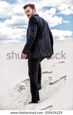 He is on his way to success. Rear view of young man in formalwear rising up by desert dune  - stock photo