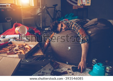 He is out. Young handsome man passed out on bean bag with joystick in his hand in messy room after party - stock photo