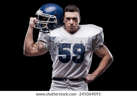 He is ready to win!  American football player looking at camera and carrying helmet on his shoulder while standing against black background  - stock photo