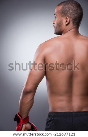 He is the best fighter. Rear view of shirtless African man in boxing gloves standing against grey background - stock photo