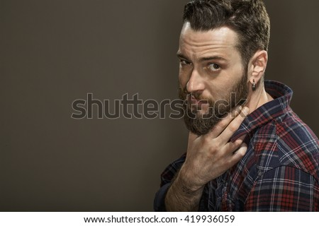 He knows you like him. Portrait of a bearded guy looking to the camera confidently touching his beard copyspace on the side on grey background. - stock photo