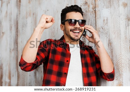 He likes good news. Portrait of cheerful young man talking on the mobile phone and smiling while standing against the wooden wall - stock photo