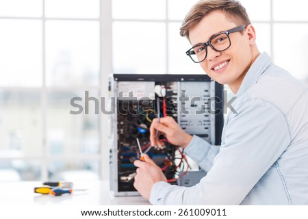 He loves his job. Portrait of handsome young man repairing computer while sitting at his working place - stock photo