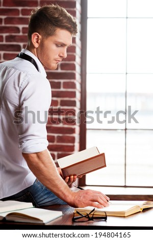 He loves studying. Handsome young man in shirt and tie writing something in note pad while sitting at his working place - stock photo