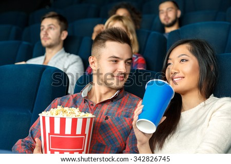 He loves to see her smiling. Young handsome man looking warmly at his girlfriend while she is enjoying her drink watching a movie in the cinema - stock photo