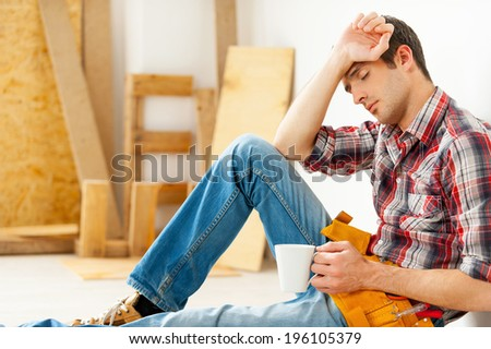 He needs a break. Tired young handyman holding cup and keeping eyes closed while sitting on the floor  - stock photo