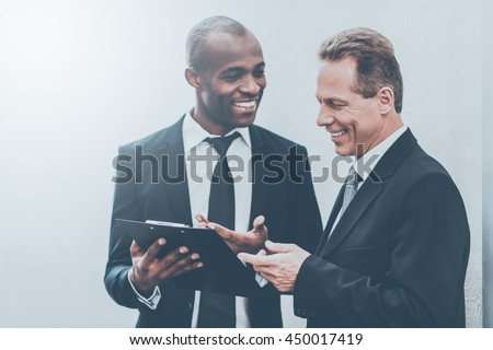 He needs an expert advice. Two cheerful business men looking at the note pad and gesturing - stock photo