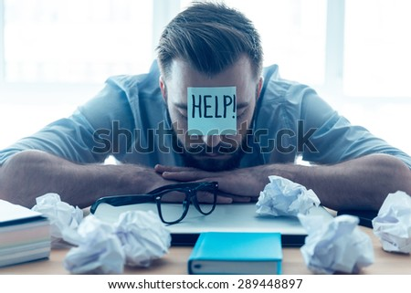 He needs help. Hopeless young beard man with adhesive note on his forehead leaning at the desk and keeping eyes closed while sitting at his working place in office