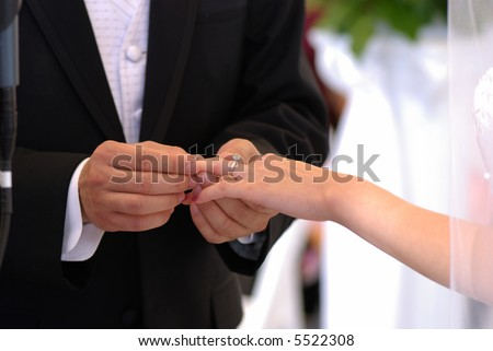 He put the wedding ring on her finger - stock photo