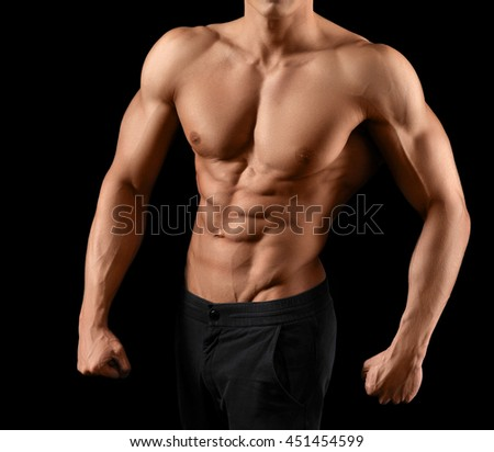 He puts a lot of work in this body. Cropped shot of a stunning hot torso of a male athlete posing on dark background - stock photo