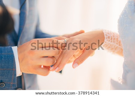 He puts on a wedding ring - stock photo