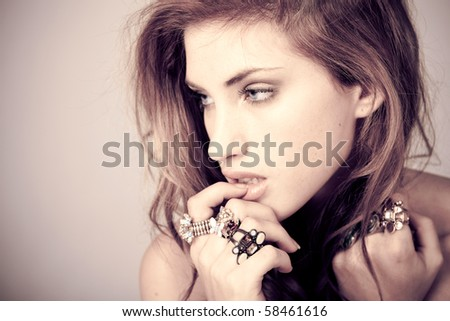 Head and shoulder portrait of a beautiful young woman wearing ornate rings on her fingers. Horizontal shot. - stock photo