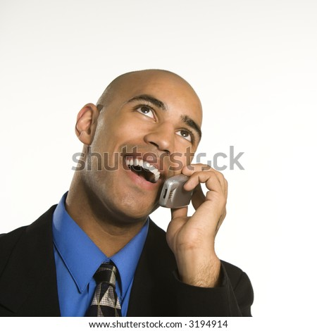 Head and shoulder portrait of African American man in suit talking on cellphone. - stock photo