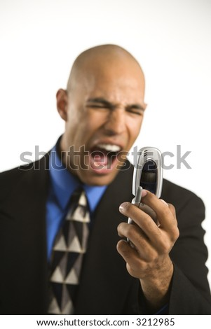 Head and shoulder portrait of African American man in suit yelling at cellphone. - stock photo